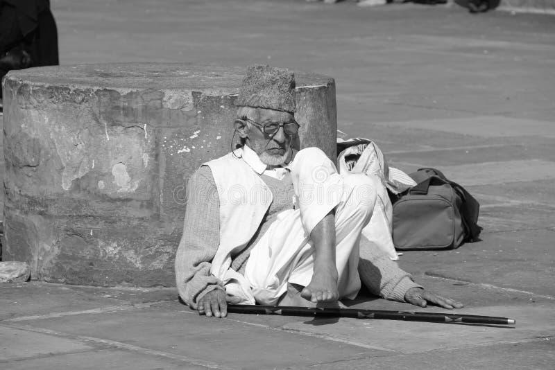 Un uomo anziano che si distende alla città universitaria di Jama Masjid immagine stock
