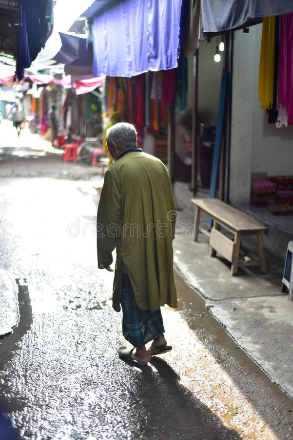 Un uomo anziano che sta intorno ad una fotografia unica del mercato urbano fotografia stock