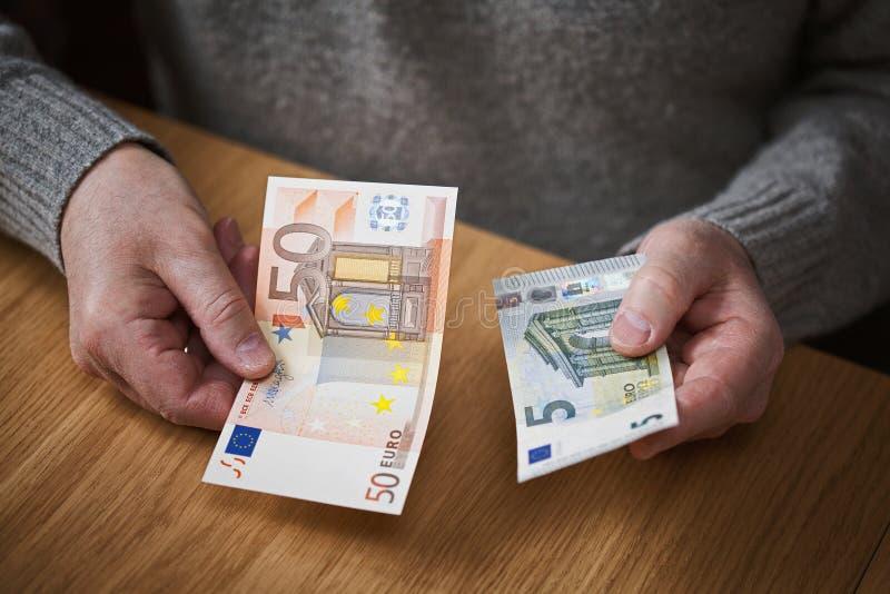 Un uomo anziano che tiene le banconote di una denominazione dell'euro dell'euro 50 e 5 immagine stock