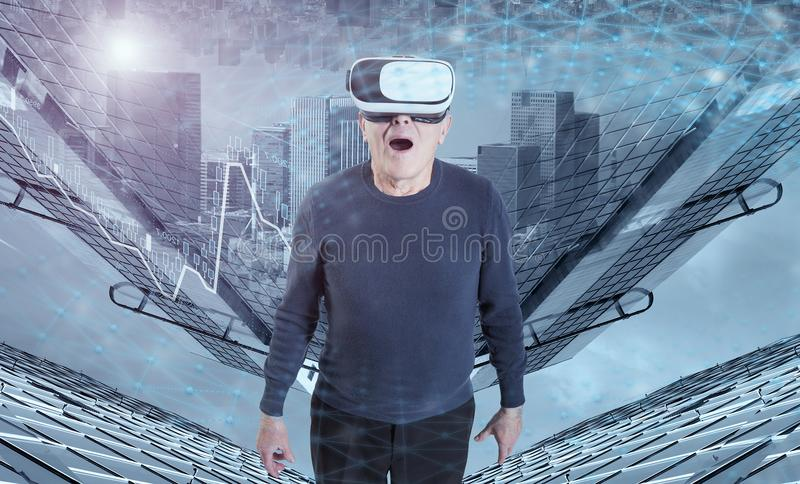 Un uomo anziano in cuffia avricolare di VR contro un fondo delle costruzioni della città fotografie stock libere da diritti