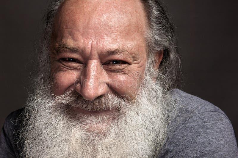Un uomo anziano dai capelli grigi di sessanta, di settanta, con capelli grigi lunghi e una grande barba bianca sorridente ampiame fotografia stock