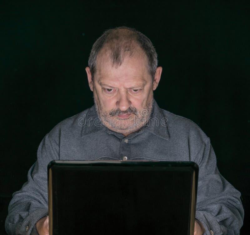Un uomo anziano lavora al computer fotografie stock