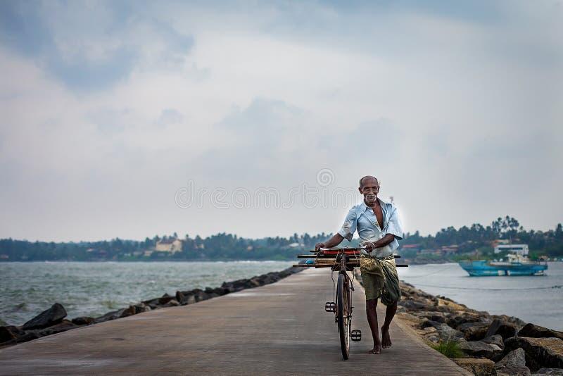 Un uomo anziano poco familiare porta una bicicletta lungo la costa dell'oceano immagini stock