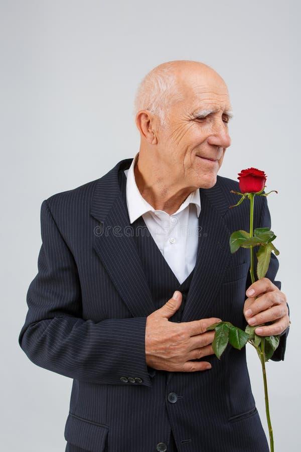 Un uomo anziano su un fondo bianco, indossante un vestito elegante nero, odora un fragrante è aumentato in sua mano fotografia stock libera da diritti