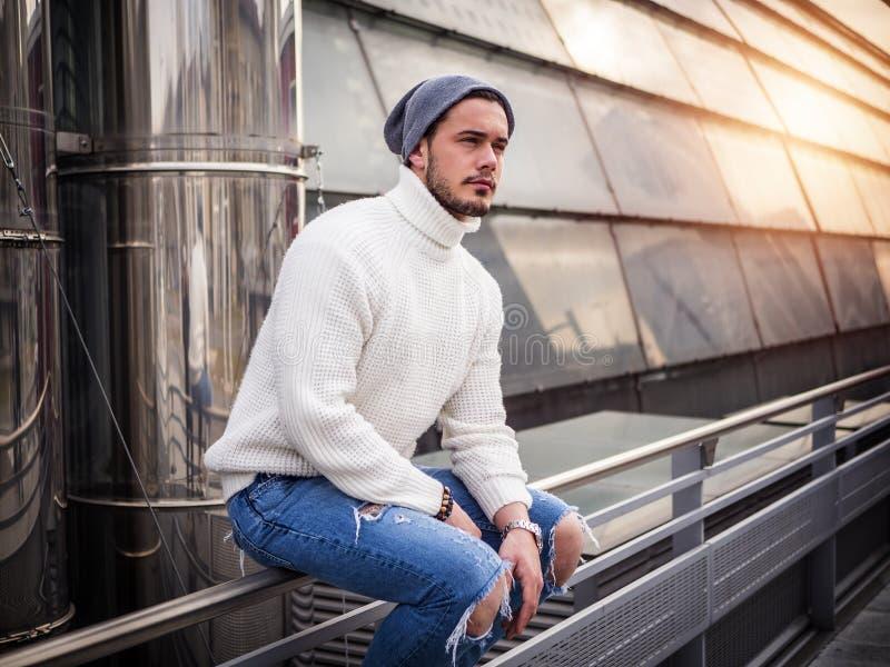 Un uomo attraente in citt? che mette maglione bianco d'uso immagine stock
