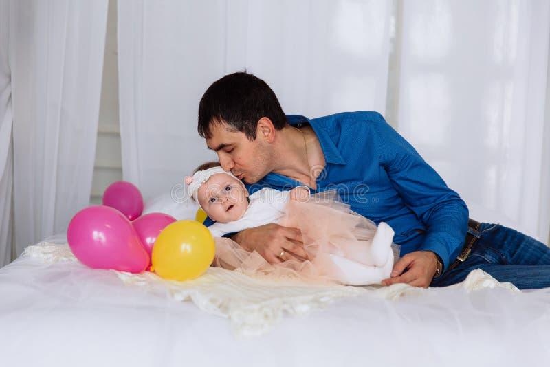 Un uomo bacia delicatamente il suo piccolo bambino che si trova sul letto Una ragazza in collant bianco ed in una gonna rosa si t immagini stock libere da diritti