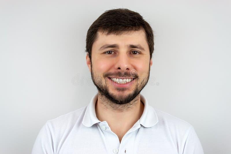 Un uomo barbuto bello felice stesso sorridente con gli occhi marroni in una maglietta bianca immagini stock