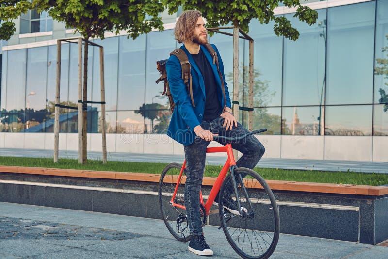Un uomo barbuto bello in jeans e rivestimento alla moda con uno zaino che si siede su una bicicletta nella città immagini stock libere da diritti