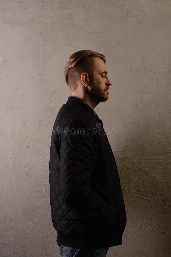 Un uomo barbuto di mezza età attraente in rivestimento nero e jeans sta dietro la parete t obliqua fotografia stock libera da diritti
