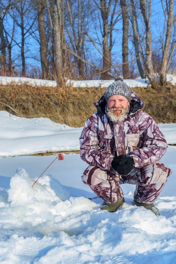 Un uomo barbuto euriopean sta pescando vicino al foro al giorno soleggiato dell'inverno sotto il cielo blu immagini stock libere da diritti