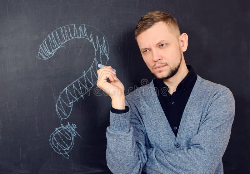 Un uomo barbuto pensa vicino ad un consiglio scolastico nero immagine stock libera da diritti