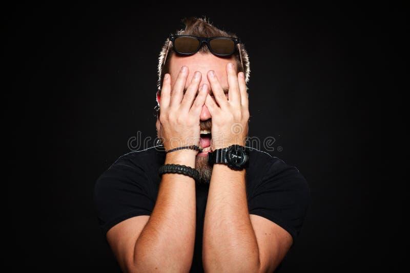 Un uomo barbuto tiene le sue mani dietro il suo fronte e grida in studio su un fondo nero fotografia stock