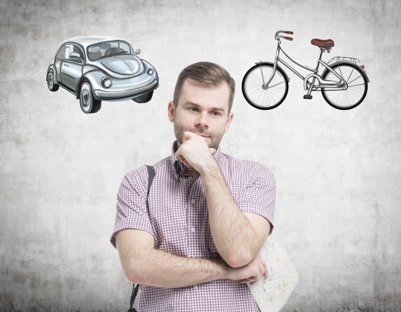Un uomo bello in camicia casuale sta provando ha scelto il modo più adatto per il viaggio o permutare Due schizzi di un'automobil fotografia stock