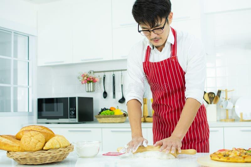 Un uomo bello che cucina nella cucina fotografia stock