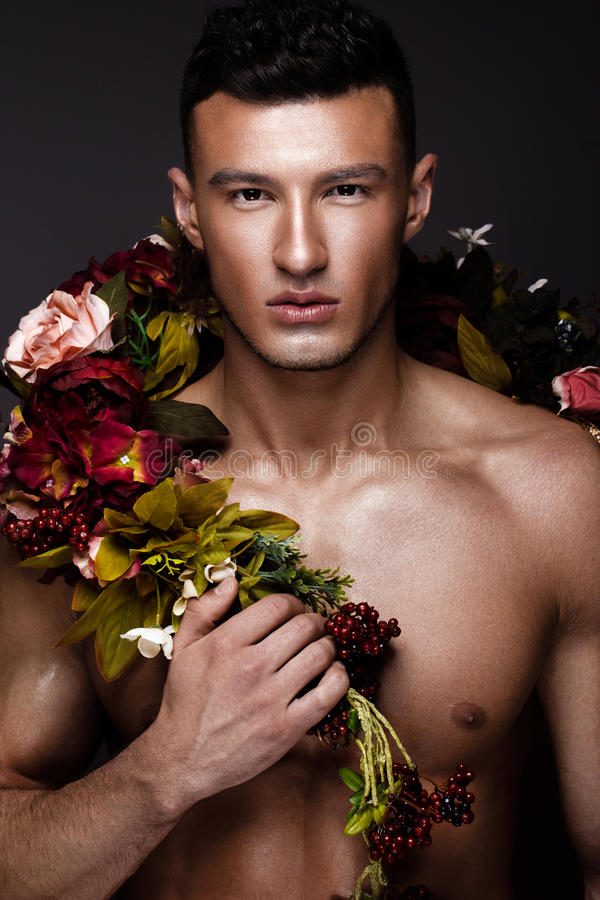 Un uomo bello con un torso, un'abbronzatura del bronzo ed i fiori nudi sul suo corpo fotografia stock