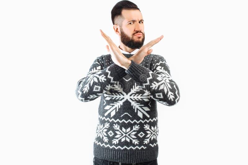 Un uomo bello con una barba, un uomo che mostra un fanale di arresto con le sue armi attraversate, un gesto della fermata immagini stock