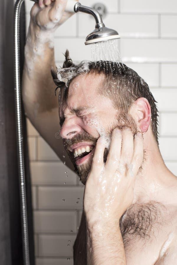Un uomo bello e barbuto lava lo sciampo dai suoi capelli in immagine stock