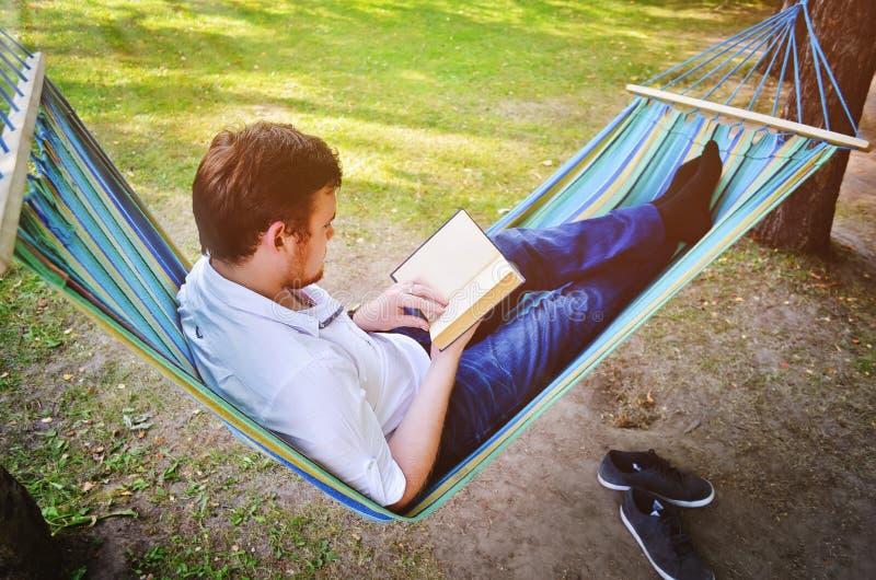 Un uomo bello legge un libro fotografia stock