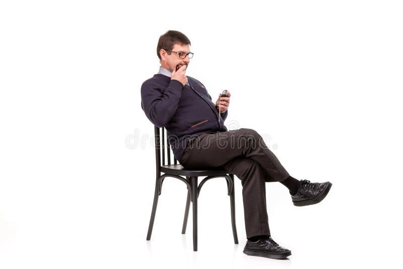 Un uomo bello in un vestito ed i vetri, si siede, con un tubo per smok fotografie stock