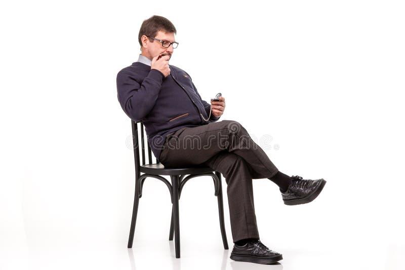 Un uomo bello in un vestito ed i vetri, si siede, con un tubo per smok immagini stock
