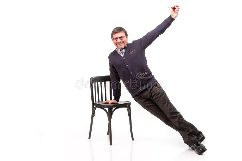 Un uomo bello in un vestito ed i vetri, si siede, con un tubo per smok fotografia stock libera da diritti