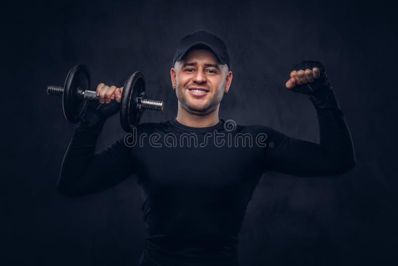 Un uomo bello, vestito negli abiti sportivi neri fotografie stock libere da diritti