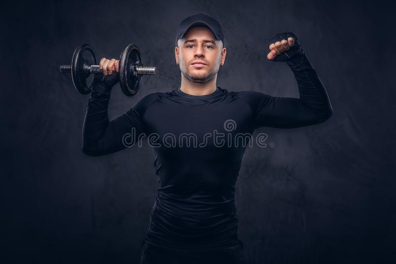 Un uomo bello, vestito negli abiti sportivi neri fotografia stock