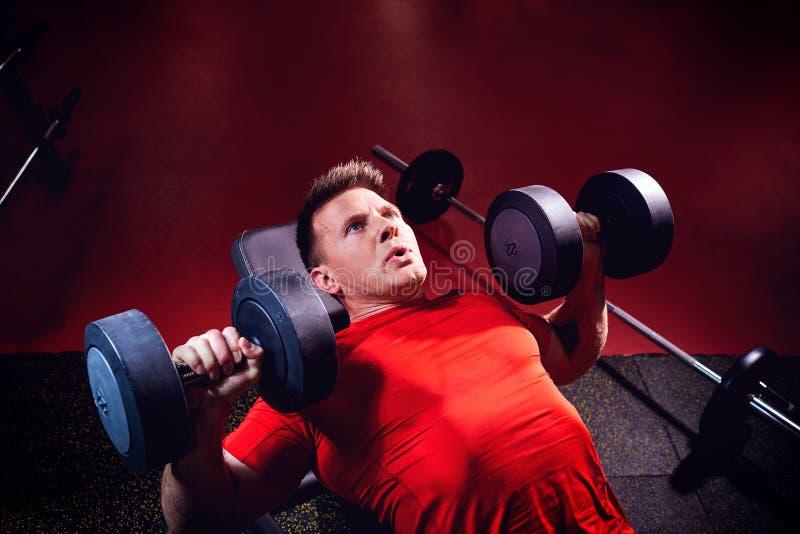 Un uomo biondo sportivo che fa gli esercizi con le teste di legno nella palestra fotografie stock libere da diritti