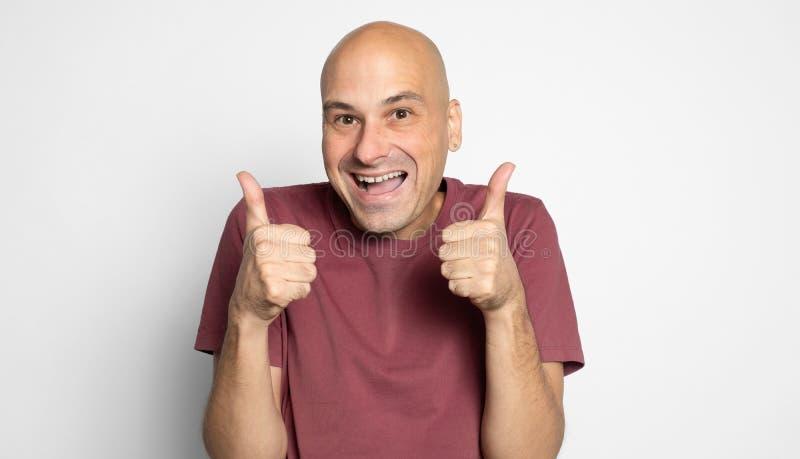 Un uomo calvo e felice fa vedere i pollici Isolato fotografie stock