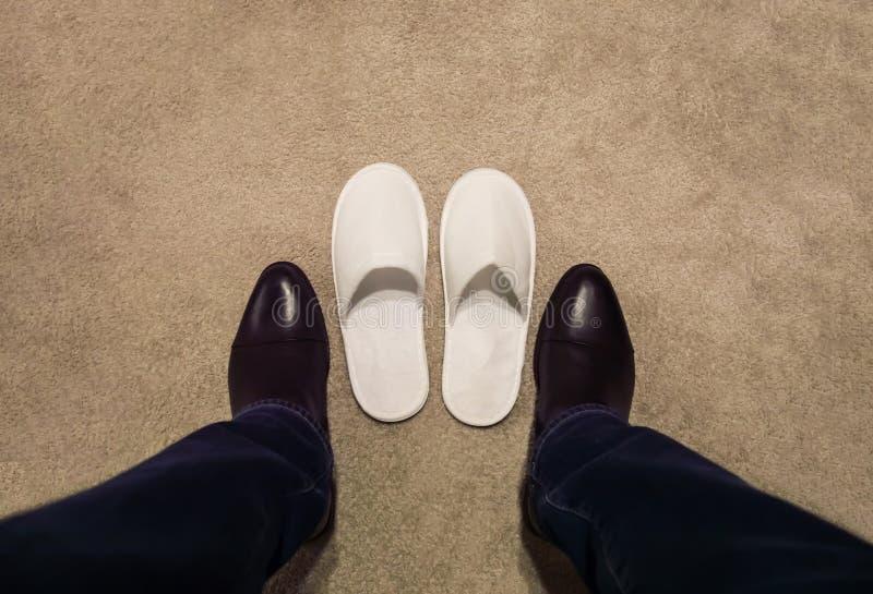 Un uomo cambia le sue scarpe, decolla le sue scarpe, lui porta le pantofole bianche immagini stock