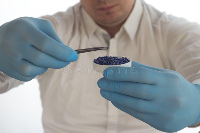 Un uomo in camice che tengono le pinzette e le palline di plastica e granelli in laboratorio fotografia stock libera da diritti