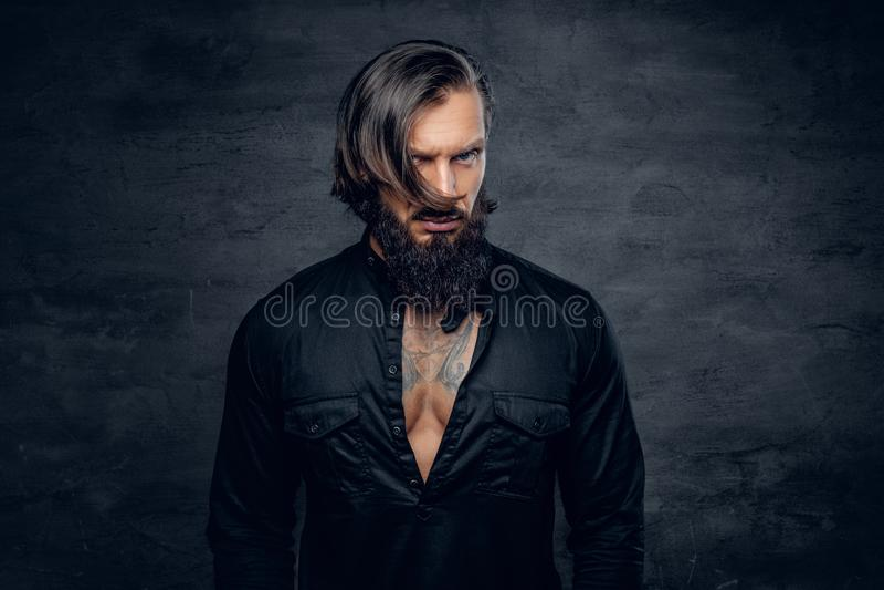 Un uomo in camicia nera con il tatuaggio sul suo petto immagini stock