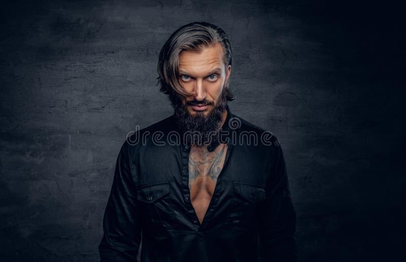 Un uomo in camicia nera con il tatuaggio sul suo petto immagine stock libera da diritti