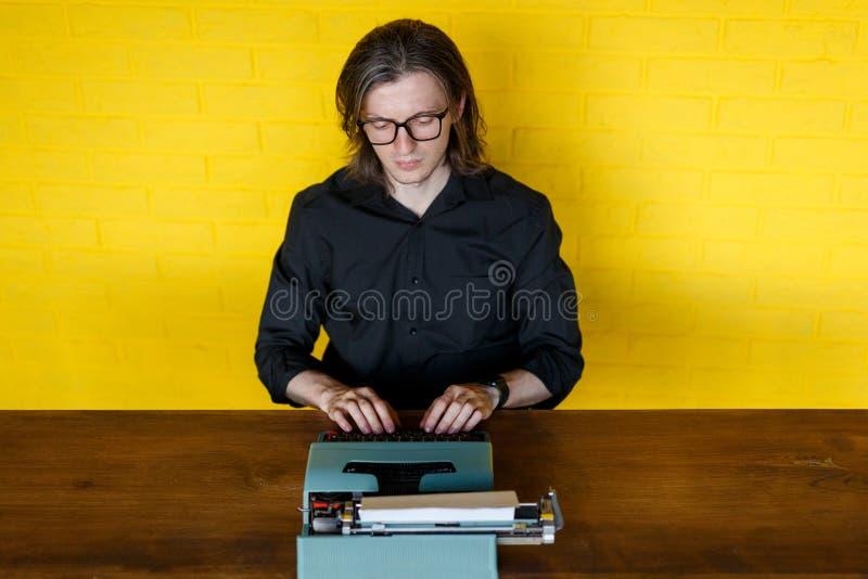 Un uomo in camicia nera, lavorante alla macchina da scrivere manuale, messa alla tavola di legno, sopra fondo giallo Copi lo spaz fotografia stock libera da diritti