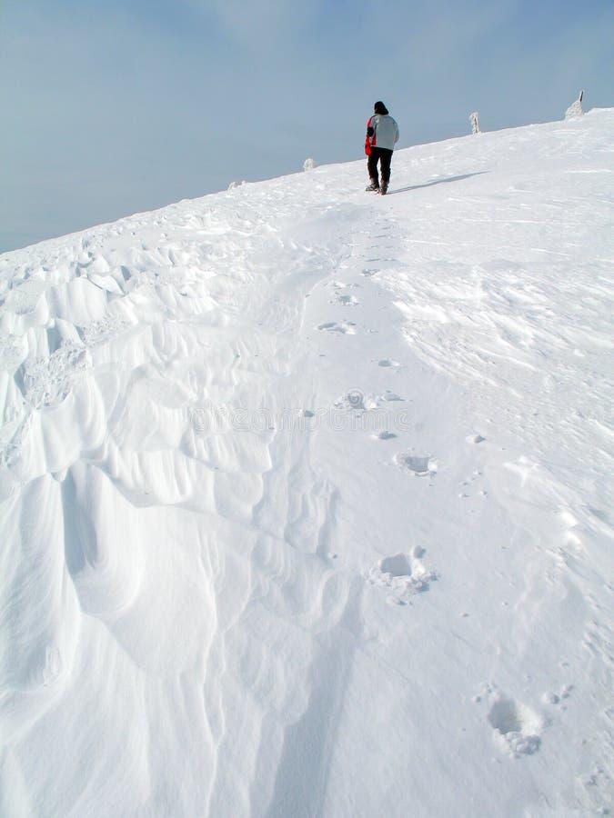 Un uomo cammina attraverso la neve fino alla cima della montagna fotografia stock libera da diritti