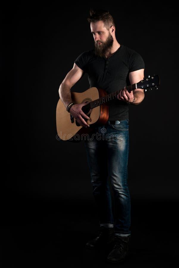 Un uomo carismatico ed alla moda con una barba sta integrale e gioca una chitarra acustica, su un fondo nero Vertic fotografia stock
