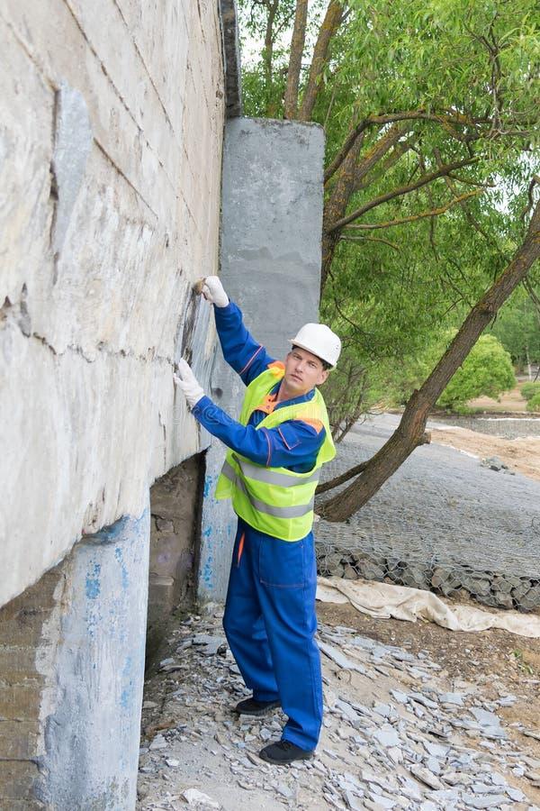 Un uomo in un casco rimuove una parete delle iscrizioni proibite fotografia stock