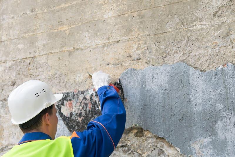 Un uomo in un casco rimuove una parete delle iscrizioni severe, vista dalla parte posteriore fotografia stock