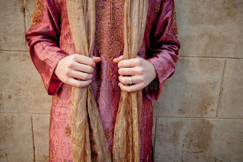 Un uomo caucasico in abbigliamento indiano tiene il suo scialle della sciarpa Kameez di Salwar fotografia stock libera da diritti