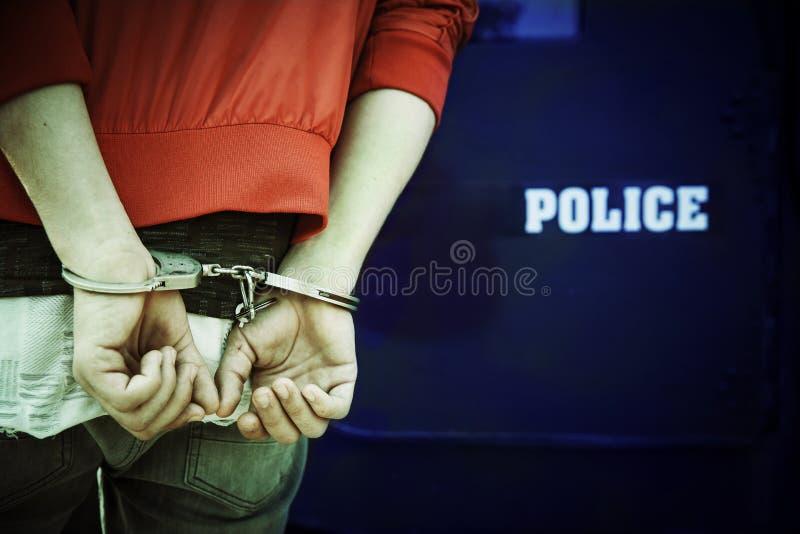 Un uomo che è arrestato ed ammanettato dalla polizia fotografia stock libera da diritti