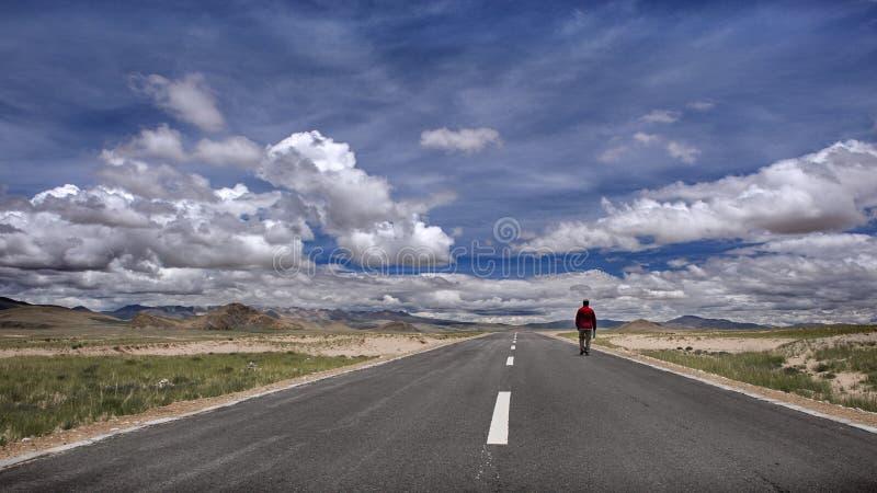 Un uomo che cammina sulla strada tibetana immagine stock