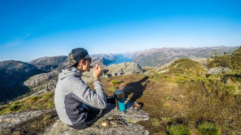 Un uomo che cucina nella regione selvaggia in Norvegia Le montagne e un fiordo è davanti lui fotografia stock