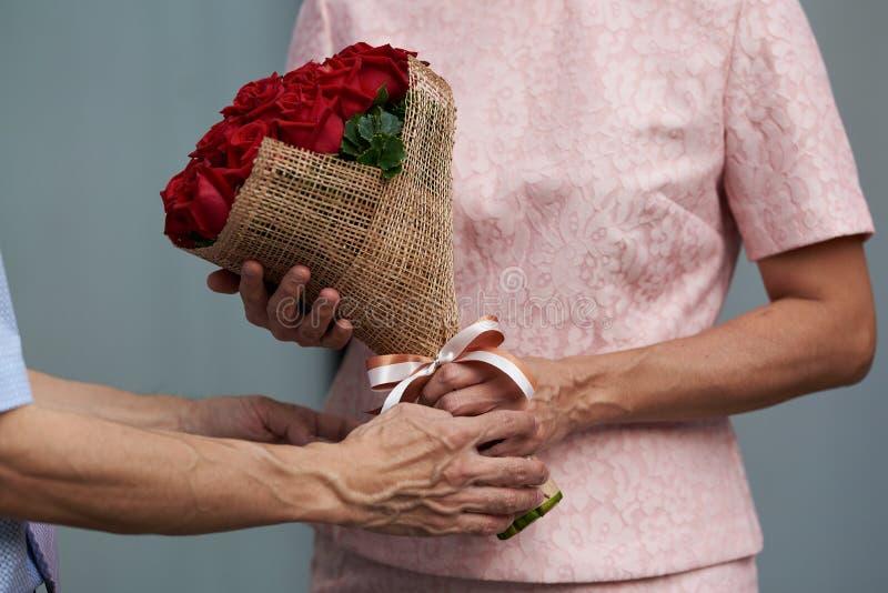 Un uomo che dà un mazzo delle rose ad una donna immagini stock libere da diritti