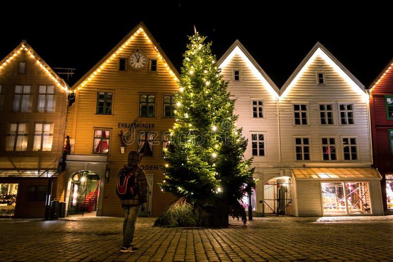 Un uomo che esamina un albero di Natale brillante davanti alle belle Camere tradizionali norvegesi a Bergen fotografia stock libera da diritti