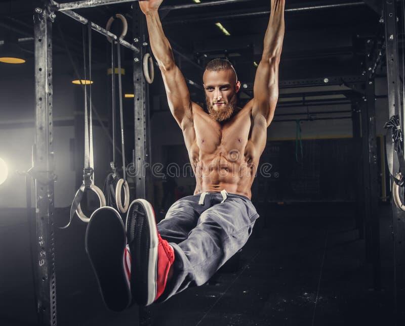 Un uomo che fa gli allenamenti dello stomaco sulla barra orizzontale fotografia stock