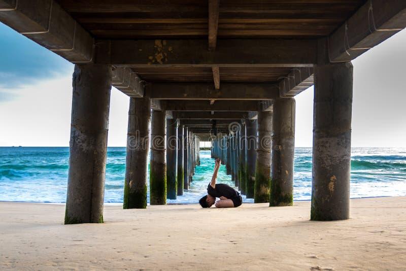 Un uomo che fa yoga sotto il pilastro alla spiaggia delle KY Co fotografia stock