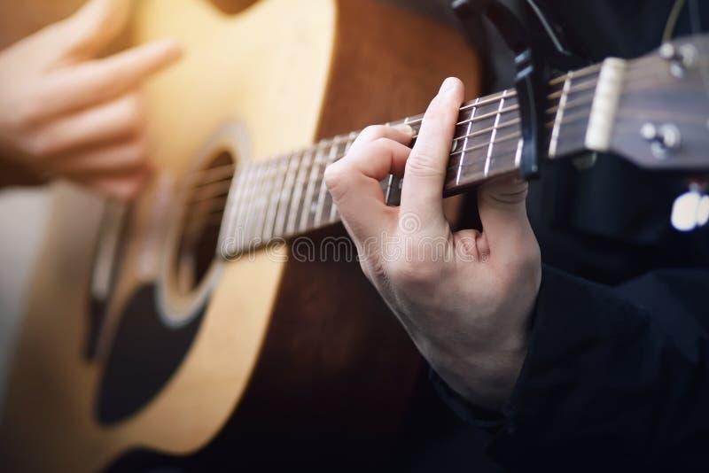 Un uomo che gioca su una chitarra acustica della sei-corda, tenente le sue corde della mano immagine stock libera da diritti