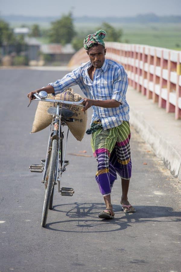 Un uomo che guida una bicicletta facendo uso dello scopo del trasporto dei tiri nel villaggio di Gorpara, Manikgonj, Bangladesh immagini stock
