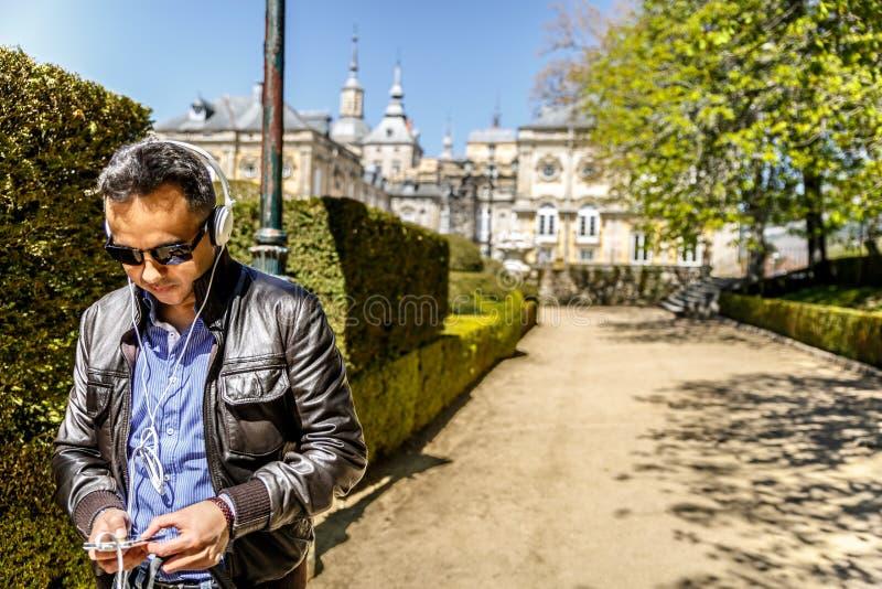 Un uomo che indossa le grandi cuffie mentre ascoltando la musica dal suo telefono cellulare, in mezzo ad un bello parco fotografia stock libera da diritti