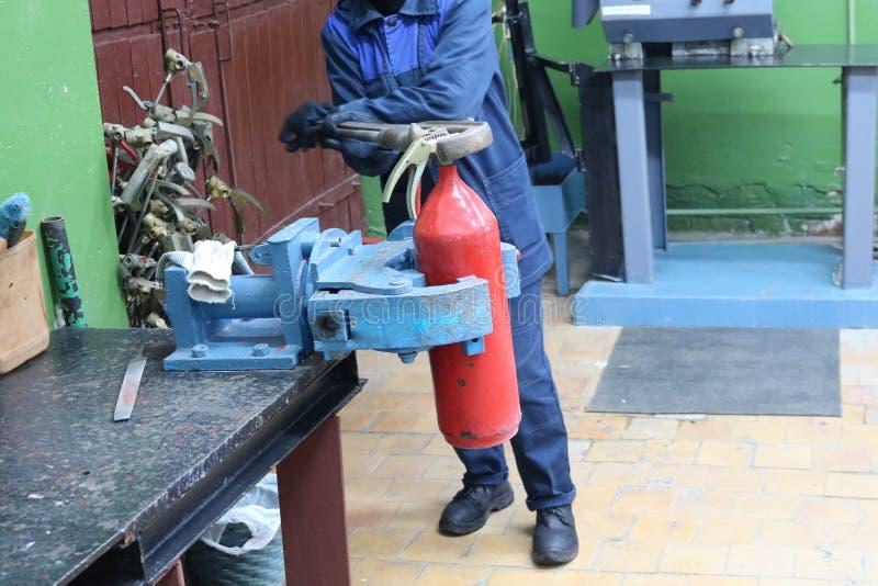Un uomo che lavora al vizio industriale con una chiave enorme del gas svita un dado su un cilindro rosso dell'estintore in un'off immagini stock